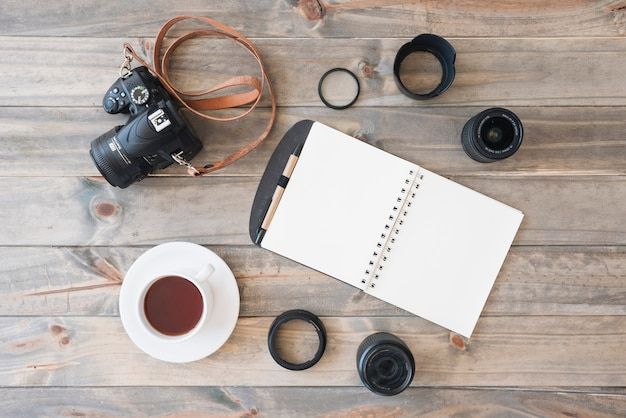 Overhead view of dslr camera; cup of tea; spiral notepad; pen; camera lens and extension rings on wooden background Free Photo