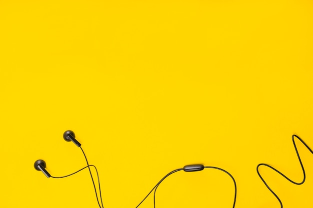 An overhead view of earphone on yellow background with space for text Premium Photo