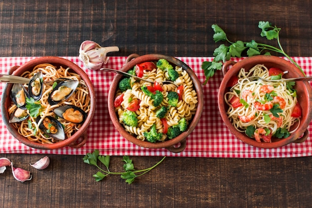 An overhead view of earthenware with different type of pasta on tablecloth Free Photo
