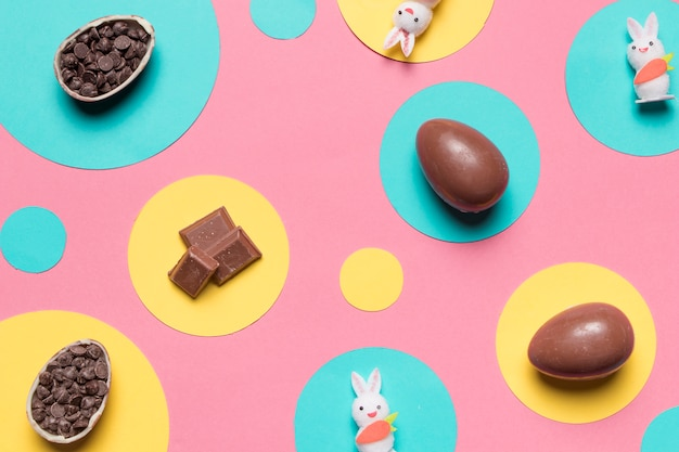 An overhead view of easter eggs; rabbit and choco chips on round frame over the pink background Free Photo