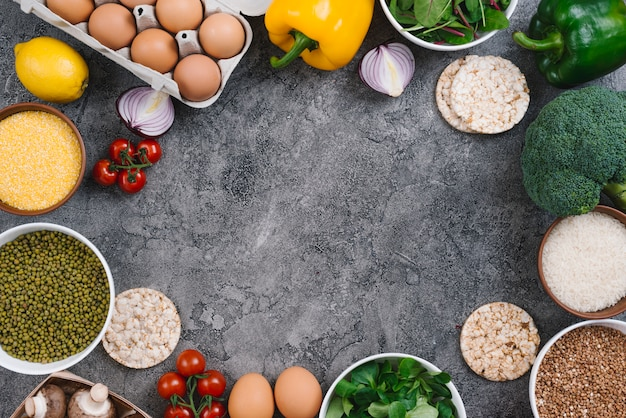 An overhead view of eggs; vegetables; polenta and mung beans bowl on concrete backdrop Free Photo
