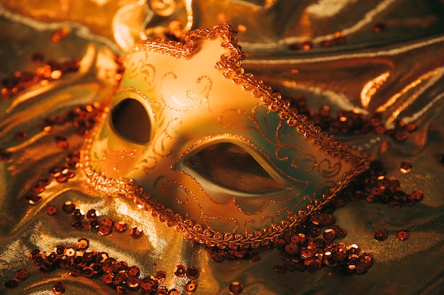 An overhead view of an elegant gold venetian mask on golden textile with sequins Free Photo