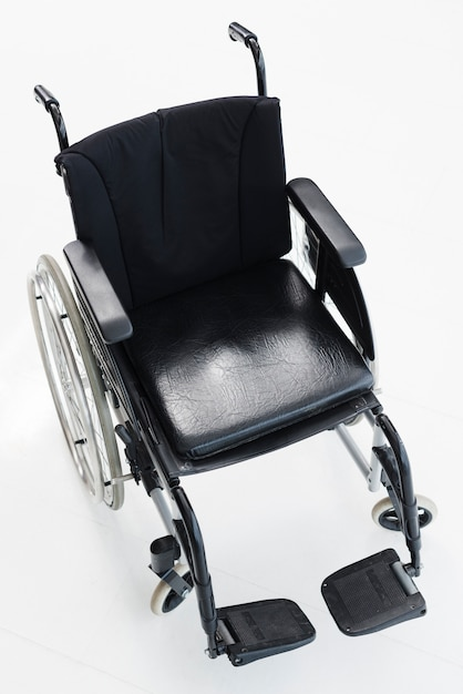 An overhead view of an empty wheelchair against white background Free Photo