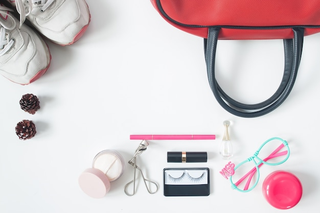 Overhead view of essential beauty items, top view of red hand bag, fashion eyeglasses, cosmetics and sneakers, top view isolated on white background Free Photo