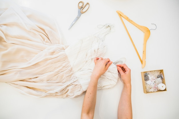 Overhead view of fashion designer's hand sewing dress Free Photo