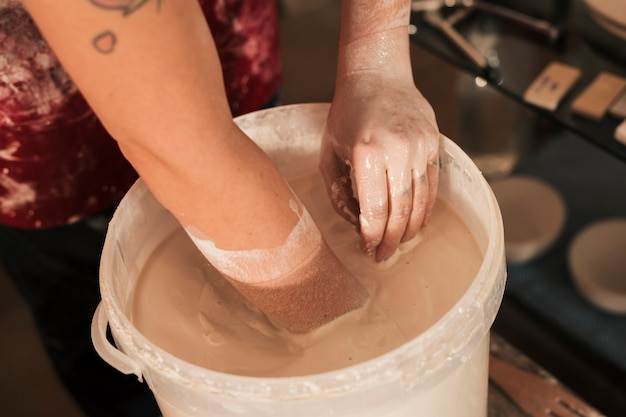 An overhead view of female potter's hand mixing the paint with hand Free Photo