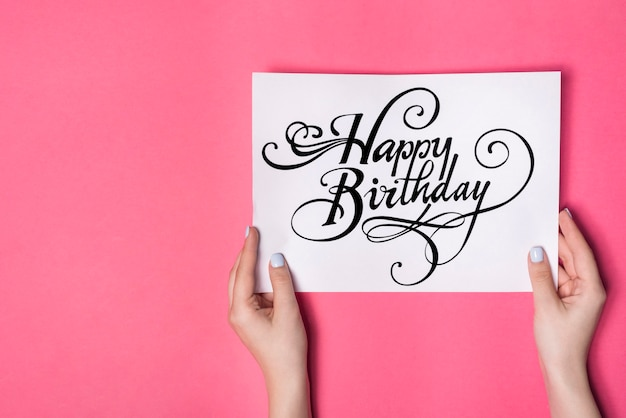 Overhead view of female's hand holding happy birthday card against pink background Free Photo