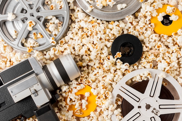 An overhead view of film reel; vintage camcorder; film reels on popcorn Free Photo