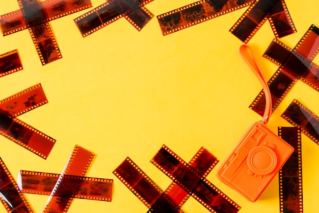 An overhead view of film strips with orange purse on yellow background Free Photo
