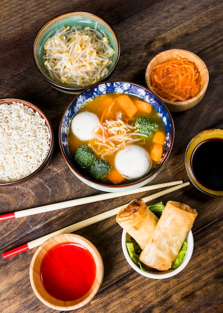An overhead view of fish ball soup; rice; beans sprouts carrot and spring rolls with sauces and chopsticks over the table Free Photo