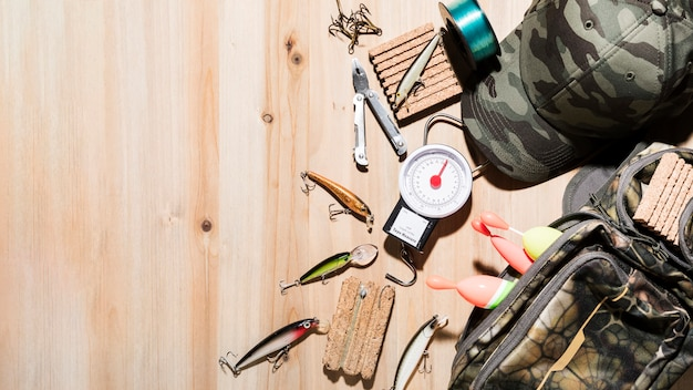 An overhead view of fishing lure; plier; fishing float with cap and bag on wooden desk Free Photo