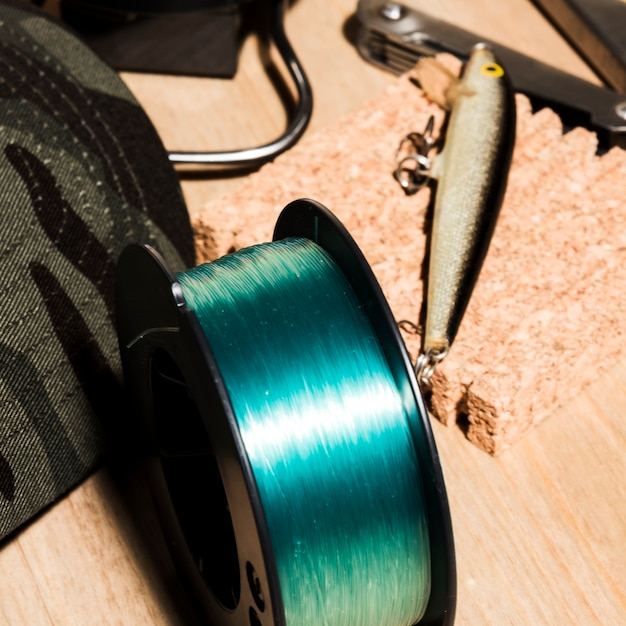 An overhead view of fishing reel and fishing baits on wooden surface Free Photo