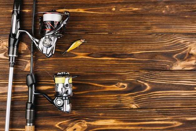 Overhead view of fishing rod and bait on wooden background Free Photo