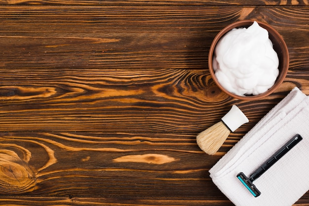 An overhead view of foam bowl; shaving brush; razor and white folded napkin against wooden textured backdrop Free Photo