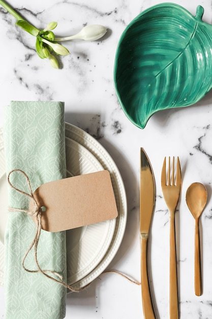 An overhead view of folded napkin tied with tag on ceramic plate and cutlery over marble textured background Free Photo