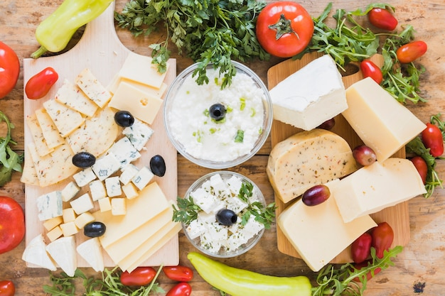 An overhead view of fresh cheese platter with olives; parsley; tomatoes and arugula leaves on wooden desk Free Photo