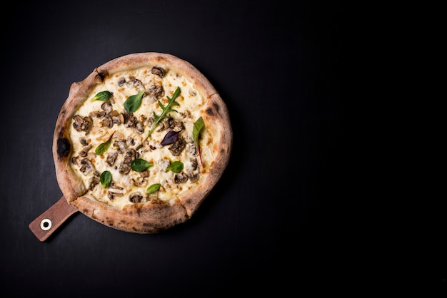 An overhead view of fresh cheesy mushroom pizza on wooden board over black kitchen worktop Free Photo