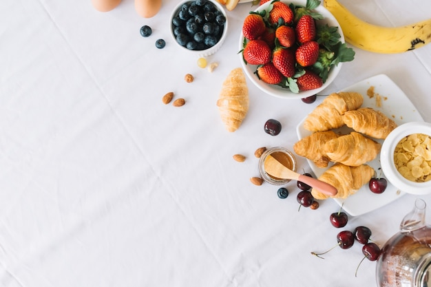 An overhead view of fresh fruits and croissant on dinning table Free Photo