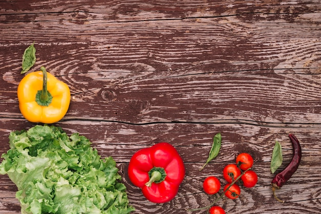 An overhead view of fresh salad ingredients on weathered wooden table Free Photo