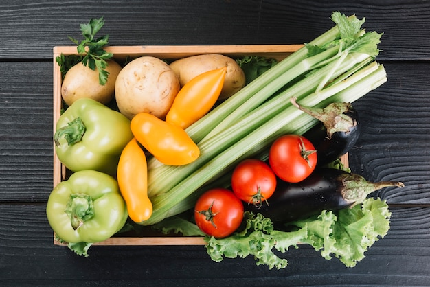 Overhead view of fresh vegetables in container on black wooden background Free Photo