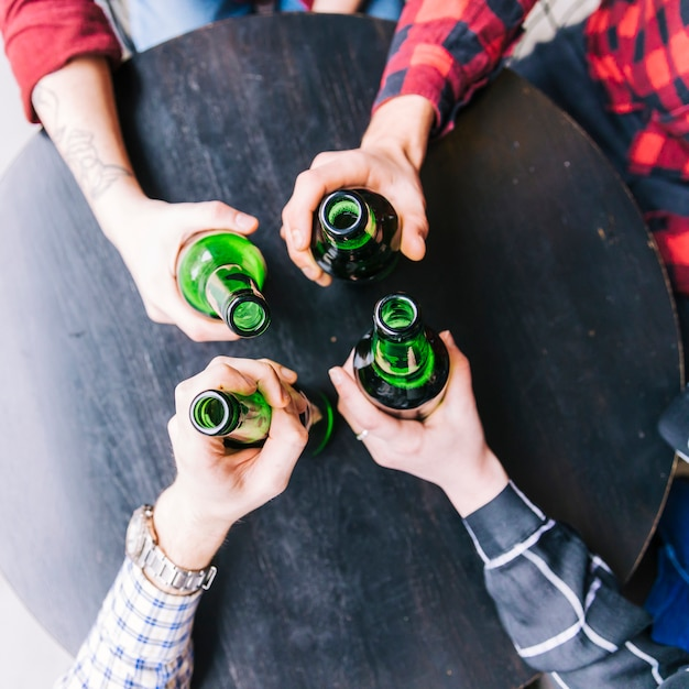 An overhead view of friend's hands holding the green beer bottles on black wooden table Free Photo