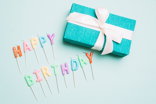 An overhead view of gift box and happy birthday candles with stick on blue backdrop Free Photo