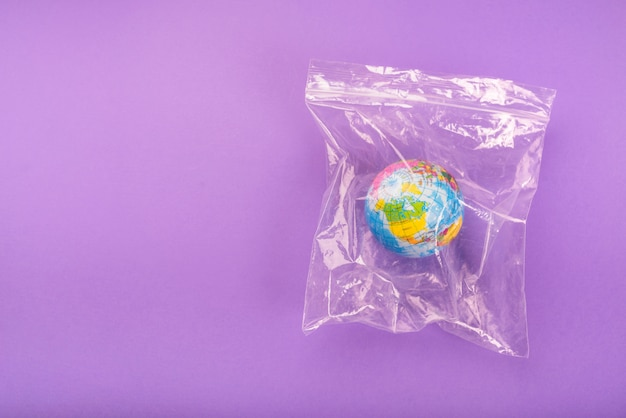 Overhead view of the globe in zip lock plastic bag over purple background Free Photo