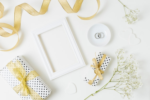 An overhead view of golden ribbon with gift boxes; frame; wedding rings and baby's-breath flowers on white backdrop Free Photo