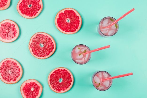 An overhead view of grapefruits slices and glass of juice with ice and mint on pastel background Free Photo