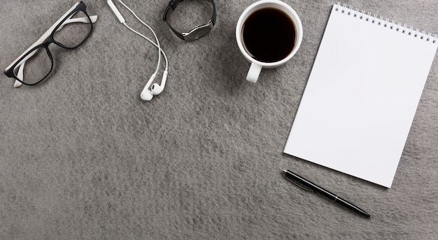 An overhead view of gray table desk with office supplies; personal accessories and coffee cup Free Photo