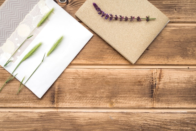 Overhead view of green ears of wheat on greeting card and lavender twig on wooden table Free Photo