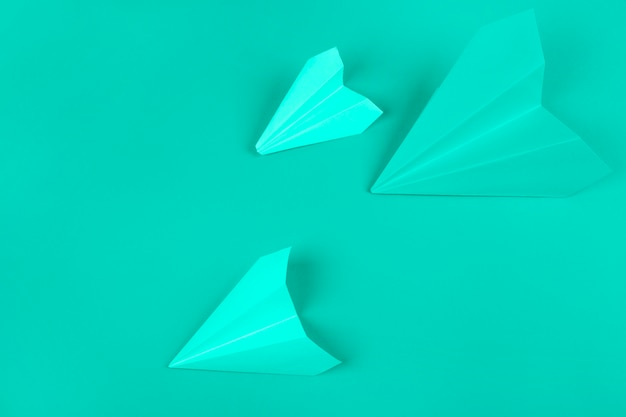 An overhead view of green paper airplanes on mint background Free Photo