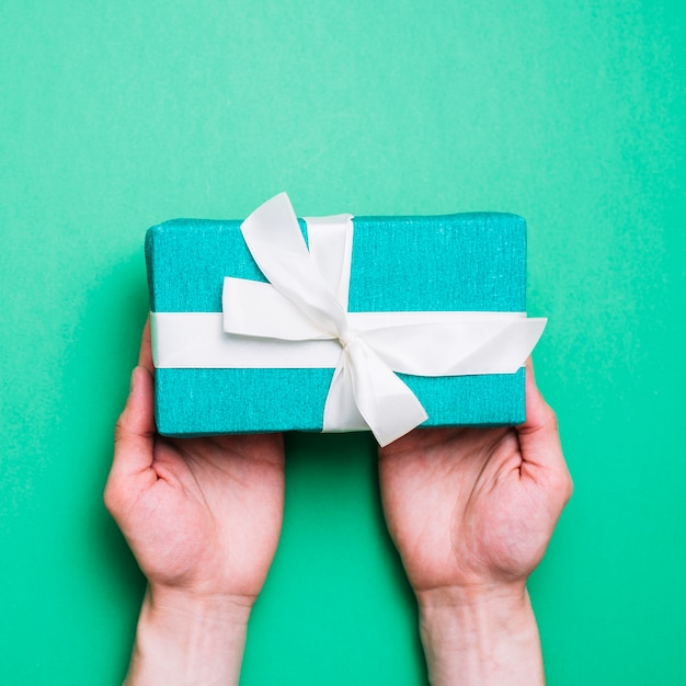 An overhead view of green wrapped gift bow with white ribbon bow on green backdrop Free Photo