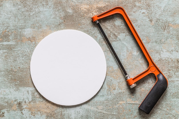 Overhead view of hacksaw and white circular frame Free Photo