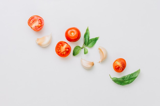 An overhead view of halved and whole cherry tomatoes; garlic cloves and basil leaf on white backdrop Free Photo