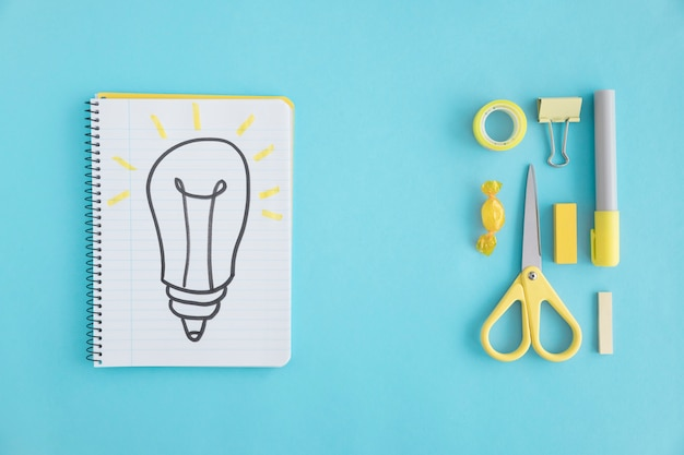 Overhead view of hand drawn light bulb on notebook with stationary on blue background Free Photo