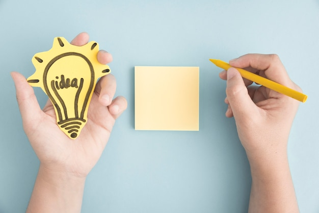 Overhead view of hand holding idea bulb writing with yellow crayon on sticky note over the gray background Free Photo