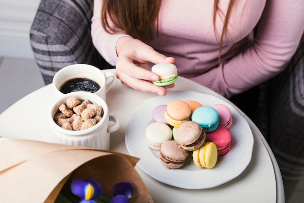 An overhead view of hand holding macaroon with brown sugar cubes and coffee cup on white table Free Photo