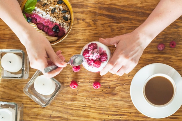An overhead view of hand holding spoon and glass of yogurt with raspberries on wooden table Free Photo
