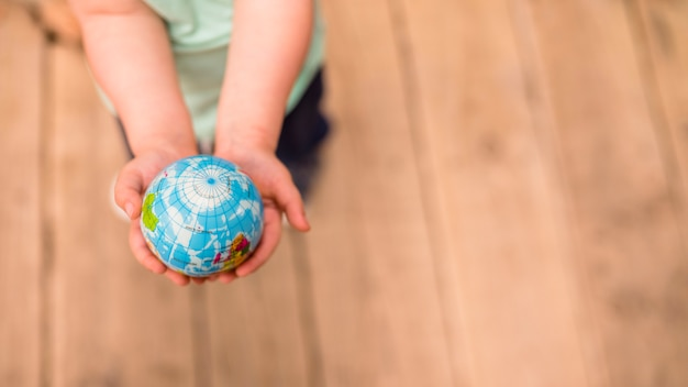 An overhead view of hands holding globe ball against hardwood floor Free Photo