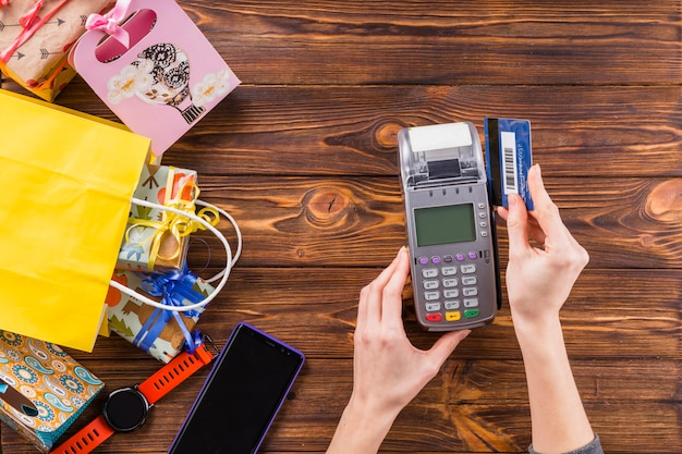 Overhead view of hands swiping credit card through payment terminal device on wooden surface Free Photo