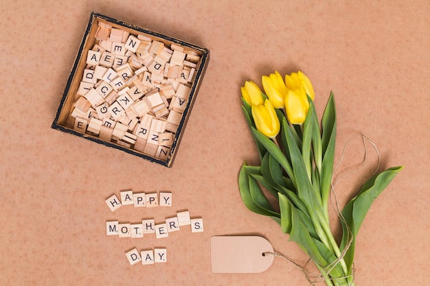 Overhead view of happy mother's day text; yellow tulip flowers; price tag and wooden blocks over brown backdrop Free Photo
