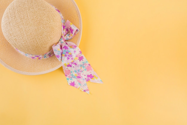 An overhead view of hat with floral ribbon bow on yellow backdrop Free Photo
