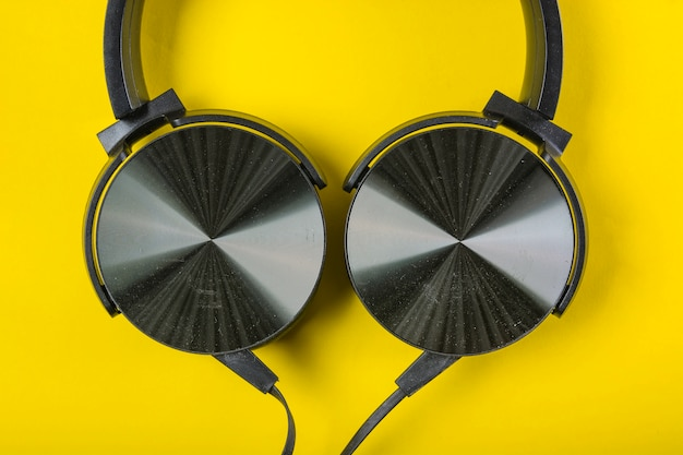 An overhead view of headphone on yellow backdrop Free Photo
