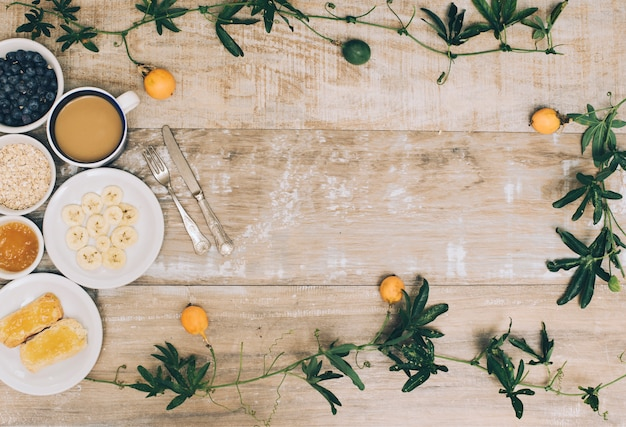 An overhead view of healthy breakfast and coffee cup with ivy on wooden table Free Photo