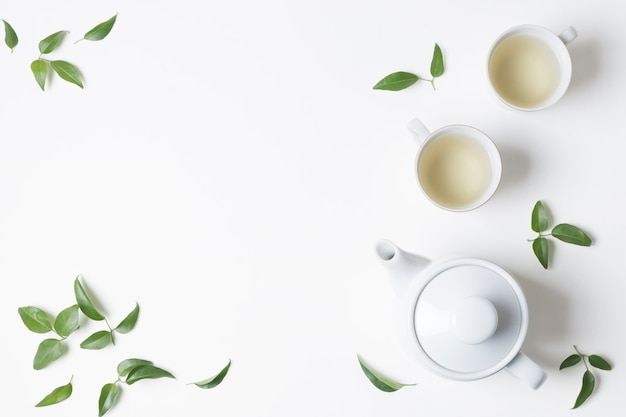 An overhead view of herbal tea cups with leaves and teapot on white background Free Photo
