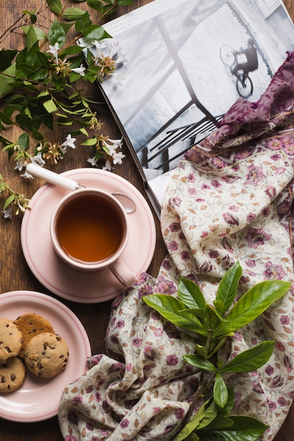 An overhead view of herbal tea with cookies; twigs; book and scarf on table Free Photo