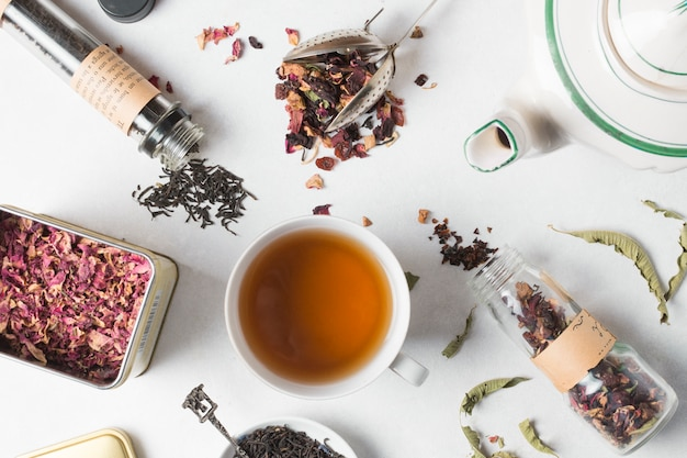 An overhead view of herbal tea with different types of herbs on white backdrop Free Photo