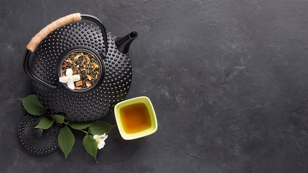 Overhead view of herbal tea with fresh white jasmine flower on black background Free Photo