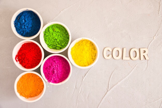 An overhead view of holi color powder with text on concrete backdrop Free Photo